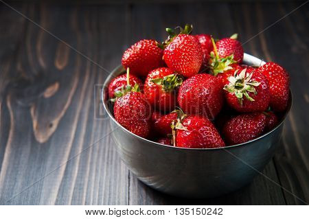 Fresh strawberries on old wooden background. Kitchen still life on table top.