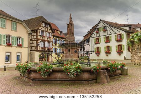 Saint-Leon fountain and traditional timbered houses in Eguisheim Alsace France
