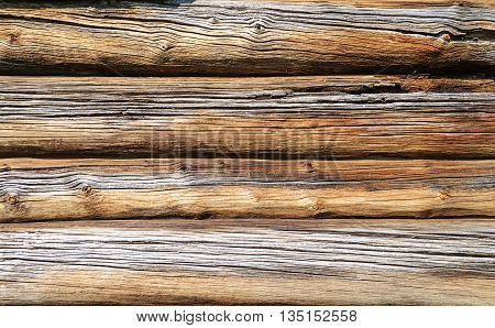 Close up of sunny old weathered log wall background