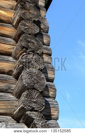 Fragment of corner of old wooden church on blue sky background