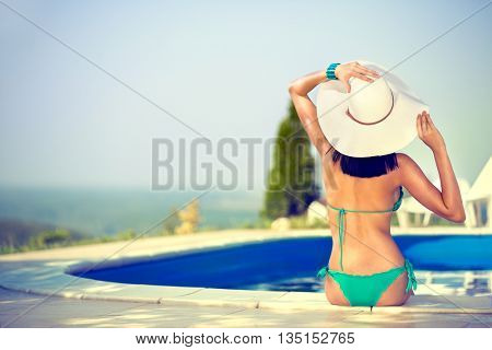 Beautiful  woman sunbathing  on the edge of the pool, back view