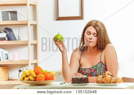 Portrait of beautiful fat woman sitting at table, holding green apple and looking at sweety cake at home. Diet concept.