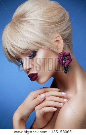 Beauty woman with beautiful make-up color . Blond hair raised hair clean skin beautiful face . Portrait shot in studio on a blue background . Borodov lip color and matching earrings in the form of a flower .