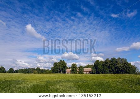 landscape with green field with high grass and blue sky with clouds. in the background is the old long, low house