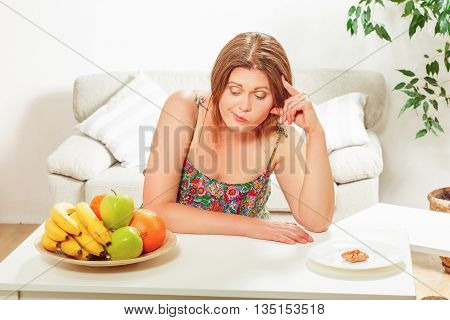 Portrait of fat woman on diet looking sad. Beautiful lady sitting at table with plate full of fresh fruits on at home.