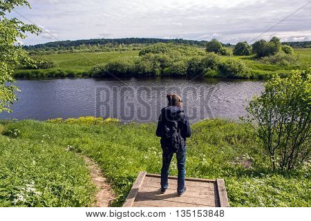 guy with backpack and dark glasses stands back and looks into the distance the expanse of the