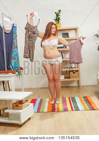 Portrait of beautiful woman trying different dresses at home. Red haired lady posing in full length in wardroom.