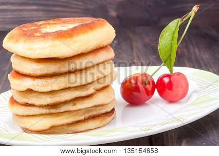 fritters on a plate with sweet cherry isolated on white background.