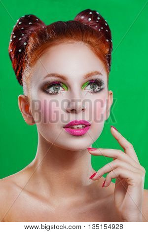 Beauty woman with a beautiful doll-colored makeup. Red hair raised hair hair in the form of a bow clear skin beautiful face . Portrait shot in the studio on a green background . Pink lips and nails .