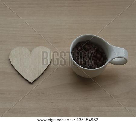 A hearth and a cup of coffee on a wooden background