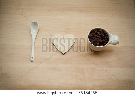 A coffee spoon a hearth and a cup of coffe on a wooden background