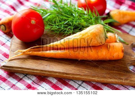 still life of carrot on the cutting board with tomato.