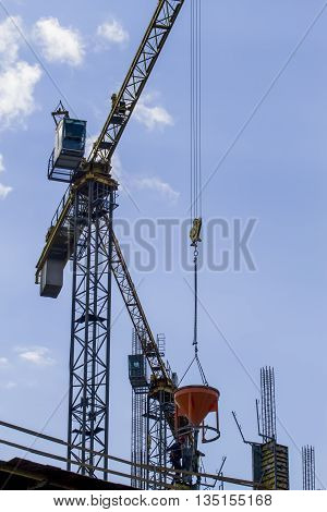 Part of yellow construction tower crane against blue sky