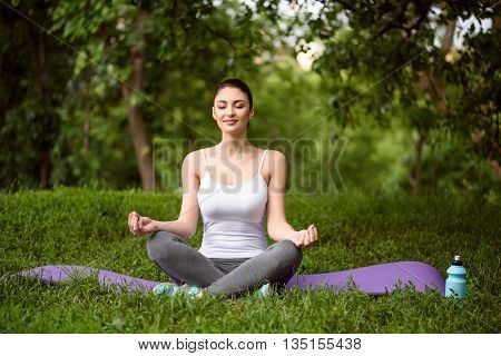 Relaxed young woman is meditating in park. She is sitting in lotus position and smiling. Her eyes are closed with pleasure