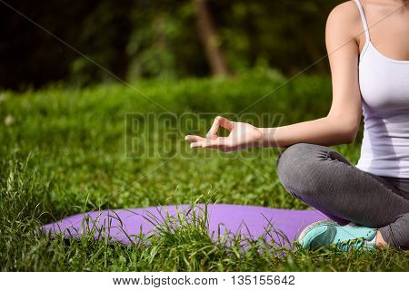 Close up of half of female body. Young is girl doing yoga and relaxing in the nature. She is sitting in lotus position while joining fingers