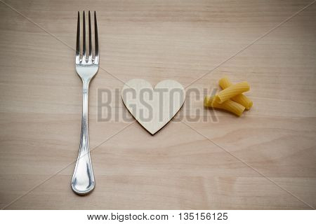 A fork hearth and pasta on a wooden background
