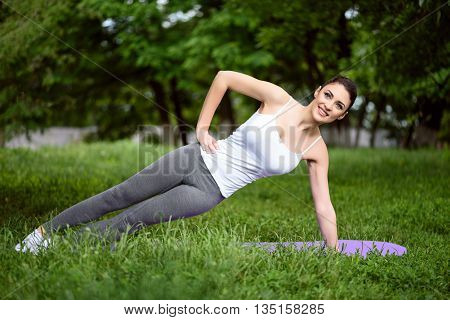 Happy young woman is doing yoga in park. She is posing with arm akimbo. Lady is looking forward and smiling