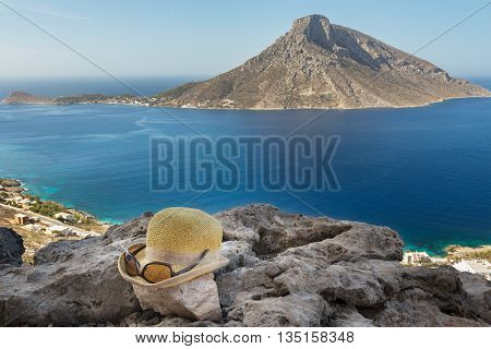 Woman straw hat and fashion sunglasses on rocky ground at outstanding natural view of Mediterranean Greek Telendos from the north side of Kalymnos island