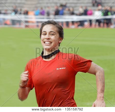 STOCKHOLM SWEDEN - MAY 14 2016: Happy woman running in the obstacle race Tough Viking Event in Sweden May 14 2016