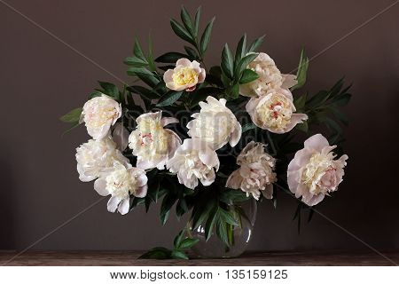 Still life with a bouquet of light pink peonies in a glass jug on a dark background.