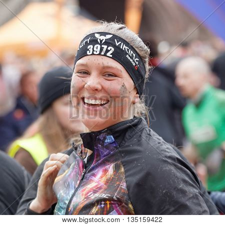 STOCKHOLM SWEDEN - MAY 14 2016: Smiling happy woman with mud in her face after finishing the obstacle race Tough Viking Event in Sweden May 14 2016