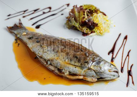 A Whole Baked Fish With Fresh Herbs And Sauce On A White Background