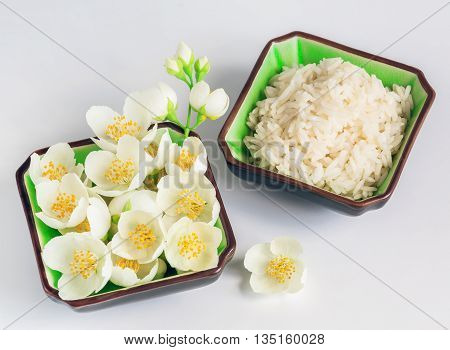 healthy power concept Eco a dish with jasmine rice and jasmine flowers on a wooden background