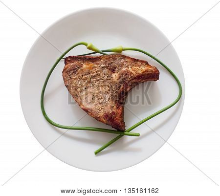 Pork Chop With Garlic Scapes On A Plate