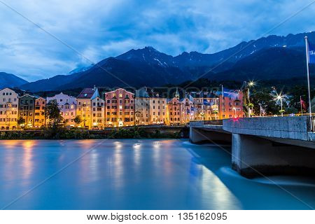 INNSBRUCK AUSTRIA - 18TH JUNE 2016: Colourful buildings along the side of the River Inn at night.