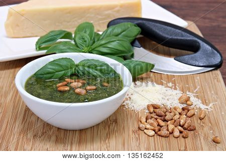A bowl of basil pesto sauce garnished with pignoli nuts on a cutting board with parmesan and a mezzaluna knife.