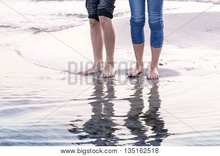 The Legs Of Tow People Reflected In The Ocean