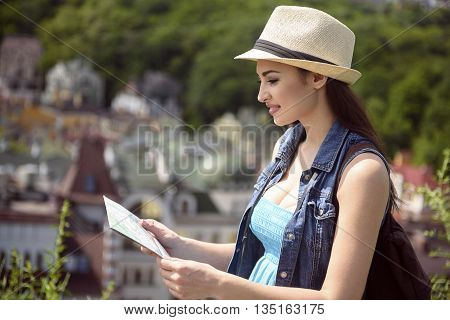 Cheerful female tourist is looking for interesting places. She is standing and reading a map. Woman is smiling happily