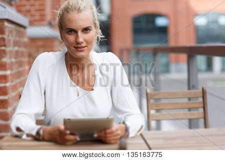 Portrait of a beautiful girl at the table with tablet. tilt-shift effect