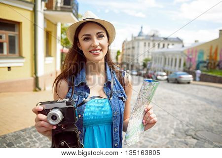 Pretty young woman is photographing town with joy. She is standing and holding a map. Tourist is looking at camera and smiling