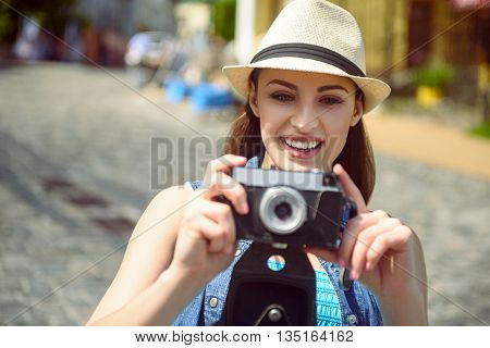 Curious female tourist is photographing city with joy. She is standing and holding a camera. Girl is looking forward and smiling