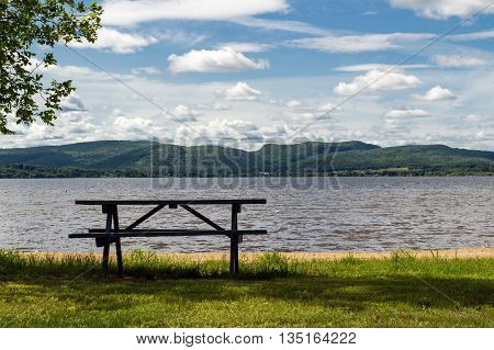 picnic table under tree shadow in front of a lake scene St-Gabriel-de-Brandon Quebec Canada