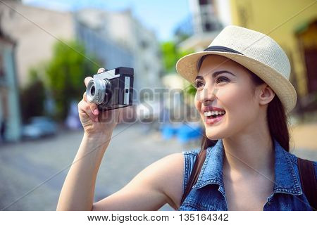 Joyful female tourist is using camera while traveling. She is standing and smiling with happiness