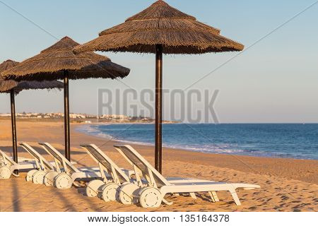 Sun beds and sun umbrellas to tourists. Portuguese beach in the Algarve.