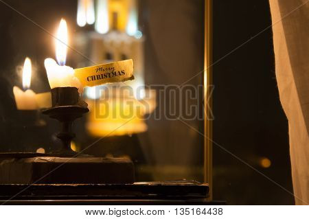 Merry Christmas concept - inscription and candle on window