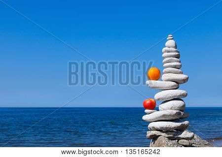 Concept of harmony and balance. Rock Zen with apple and orange in the background of summer sea