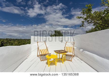 Place to relax on a porch on vacation. A board game on the table.