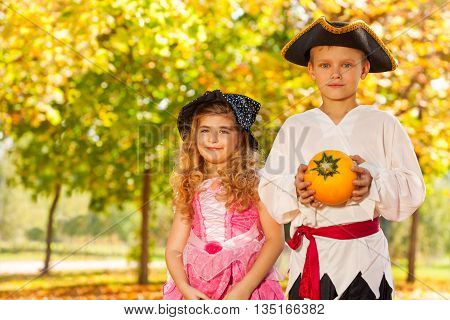 Happy boy and girl in Halloween costumes with small pumpkin and buckets in the forest during sunny autumn day time