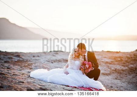 Charming Bride And Elegant Groom On Landscapes Of Mountains And Suset At Lake