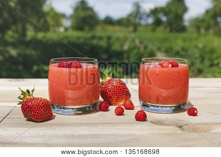 A glass of strawberry smoothie on a wooden table with mint in the garden