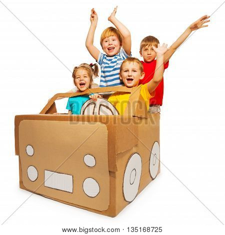Four happy kids waving their hands sitting in toy cardboard car, isolated on white