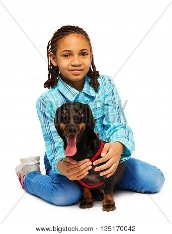 African American girl hugging friendly small dachshund isolated on white