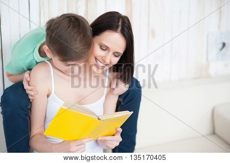 See how interesting. Smiling mother and her adult son reading book, spending time at home