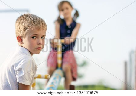 Children playing on swing. Boy in focus and girl blurred behind.