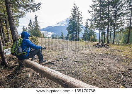 Lonely hiker traveler sitting on a log waching mountain scenery