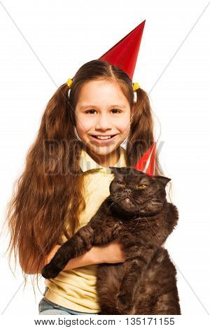 Happy little girl with black cat and wearing party birthday cap as well as pet isolated on white
